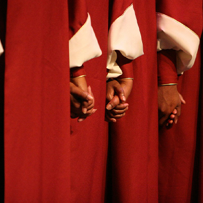 Cropped body picture of 3 people dressed in red and white choir robes