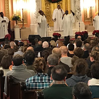 Large crowd of people enjoying the choir all dressed in white at the front of the church